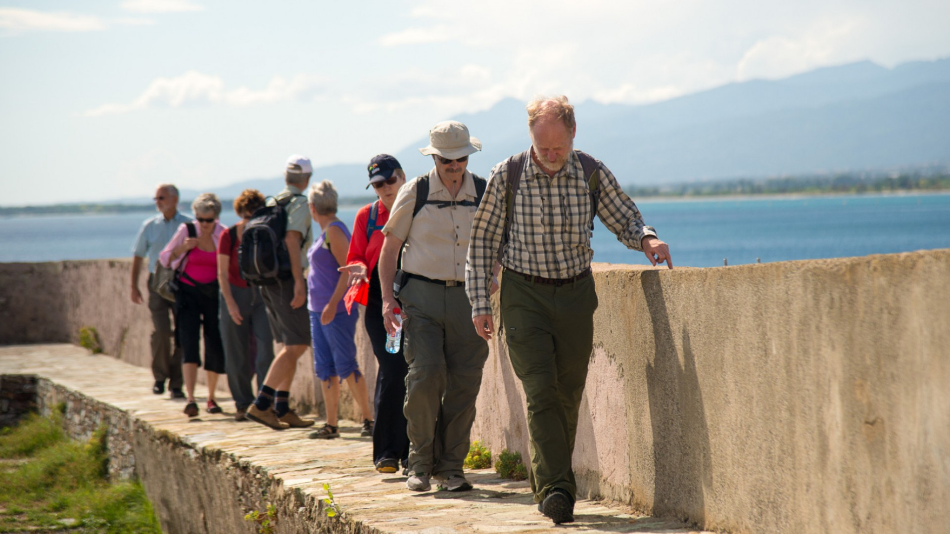 group walking along sidewalk with wall in corsica