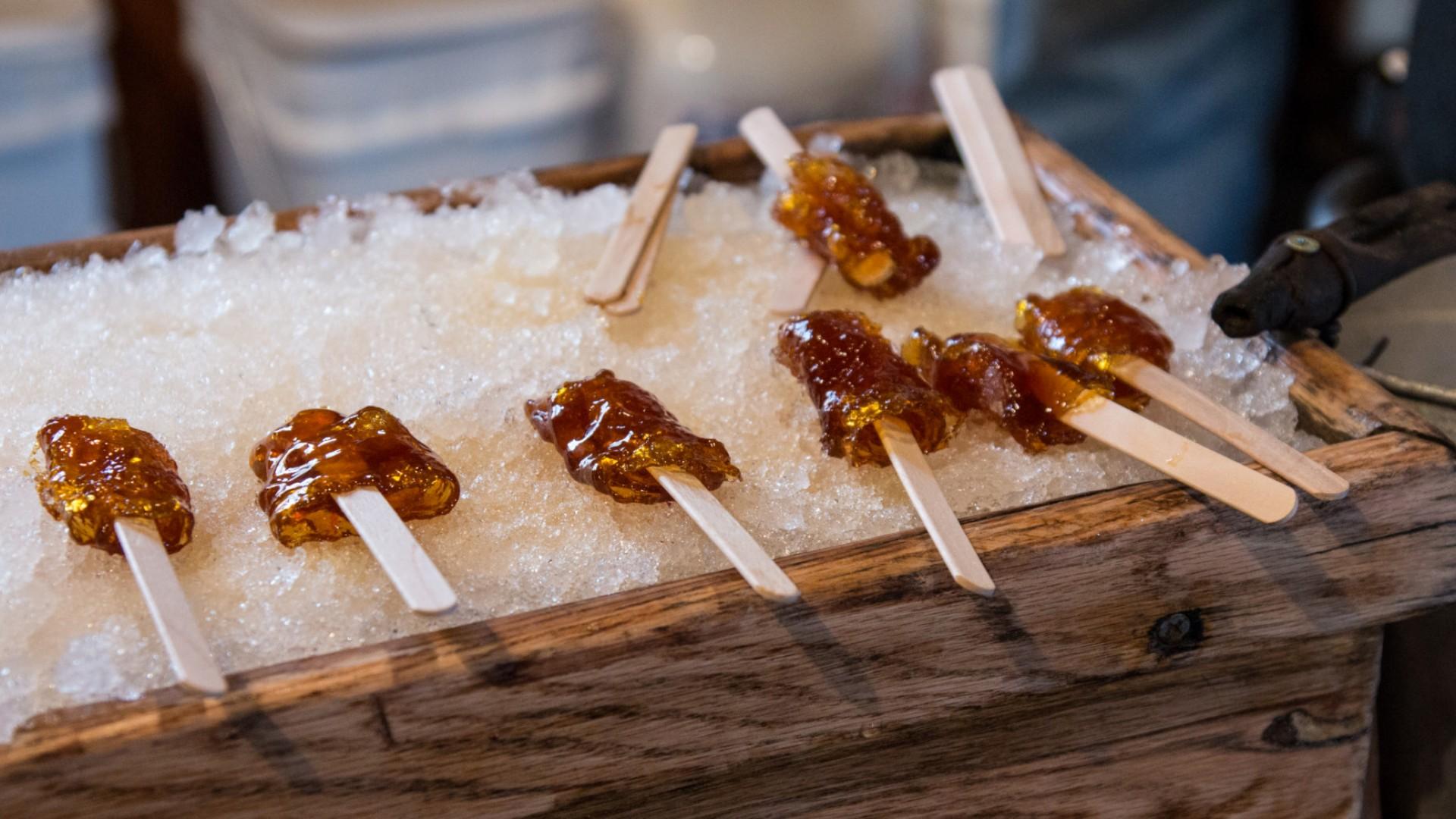 maple syrub taffy on sticks sitting on ice