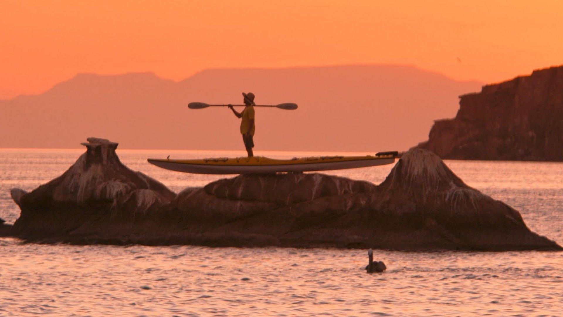 sea kayaker in sunset on rocks in LaPaz baja